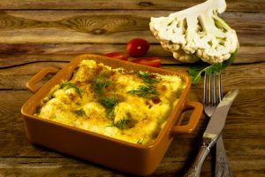 Baked cauliflower in breadcrumbs with cheese on a square ceramic baking dish, fork, knife, tomatoes, wooden background, horizontal